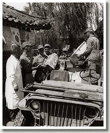Warrant Officer, Second Class Maurice Rice Juteau, 2nd Battalion, Royal 22e Regiment, Distributing Food to Refugees, Korea, 3 July 1951.