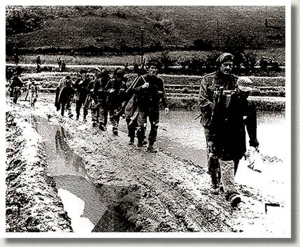 Column of Royal 22e Regiment Soldiers Slogs over a Muddy Ridge, North Korea, 20 June 1951.